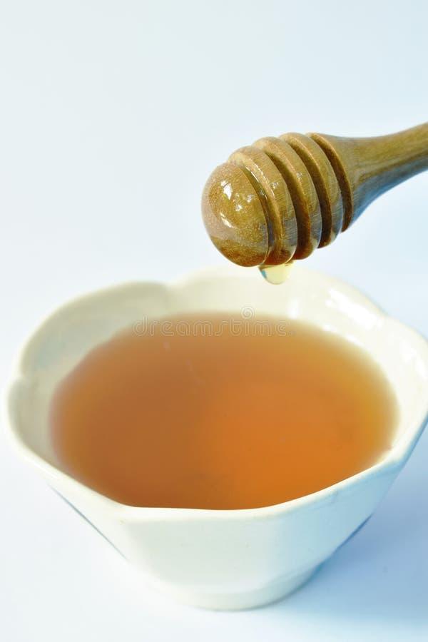 Honing op houten lepeldaling aan kop op witte achtergrond stock fotografie