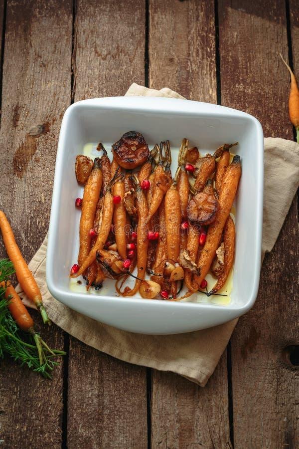 Honing verglaasde wortelen met knoflook en orego, exemplaarruimte stock foto