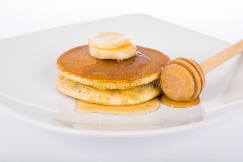 Honingsdalingen op pannekoeken en bananen royalty-vrije stock foto's
