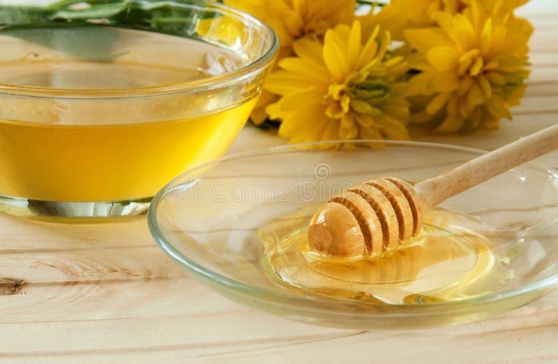 honingsdipper in een glasplaat op houten lijst stock afbeeldingen