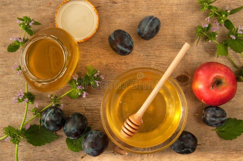 Honingsdipper in een glasschotel op een houten lijst met vruchten en gebied bloeit royalty-vrije stock fotografie