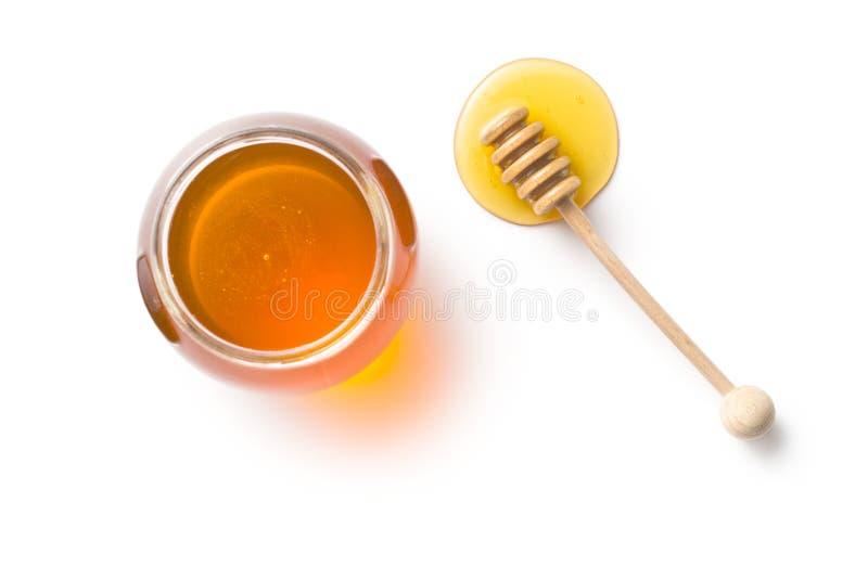 Honingsdipper en honing in kruik royalty-vrije stock afbeeldingen