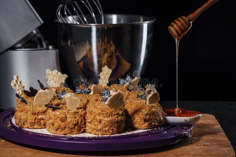 Honingsmuffins op een tribune op een houten keukenlijst naast een mixer en een houten lepel met stromende honing royalty-vrije stock afbeelding