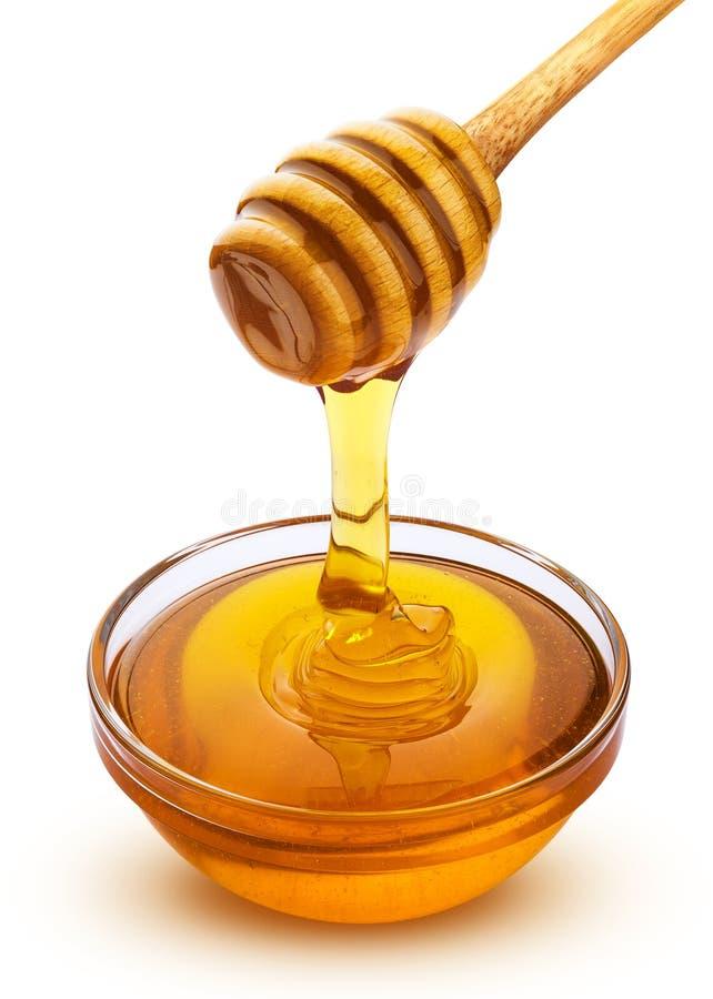 Honingsstok en kom het gieten van honing op witte achtergrond met het knippen van weg wordt geïsoleerd die stock foto