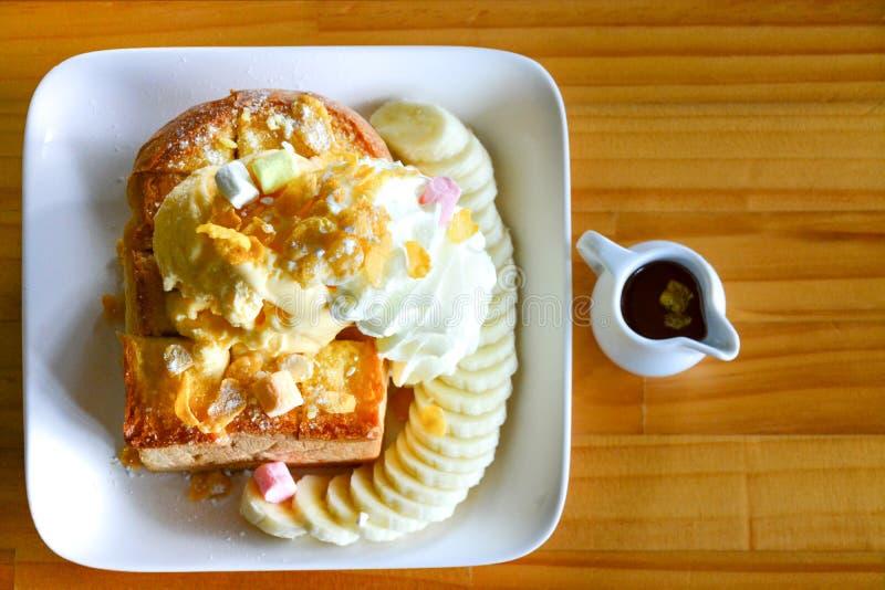 Honingstoost met vanilleroomijs en heemst bij slagroom, met banaan en chocoladestroop wordt de gediend die royalty-vrije stock afbeelding