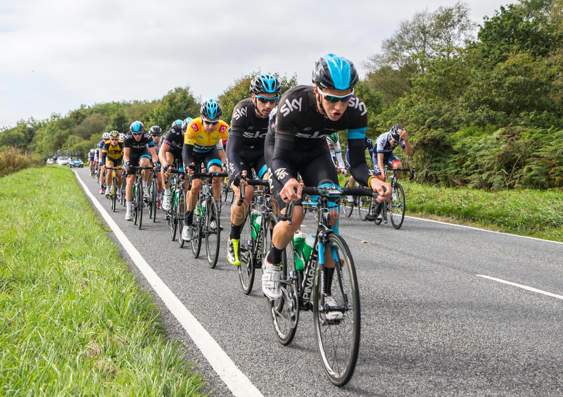 2013 Tour of Britain Cycle Race. HONITON, UK - SEPTEMBER 20: Bradley Wiggins wears the IG Yellow Jersey as current tour leader, in the pack of the Devon stage of stock images