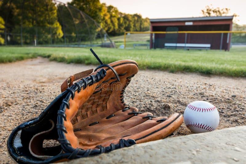 Honkbal en handschoen op gras in de vroege lente van de ochtenddauw stock foto's
