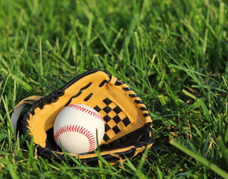 Honkbal in gele handschoen op het gras royalty-vrije stock foto's