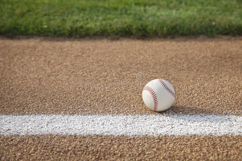 Honkbal op basisweg met gras infield stock foto's