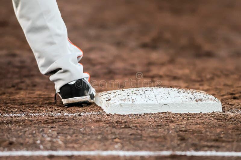 Honkbalspeler met is hij voeten wat betreft de grondplaat stock afbeeldingen