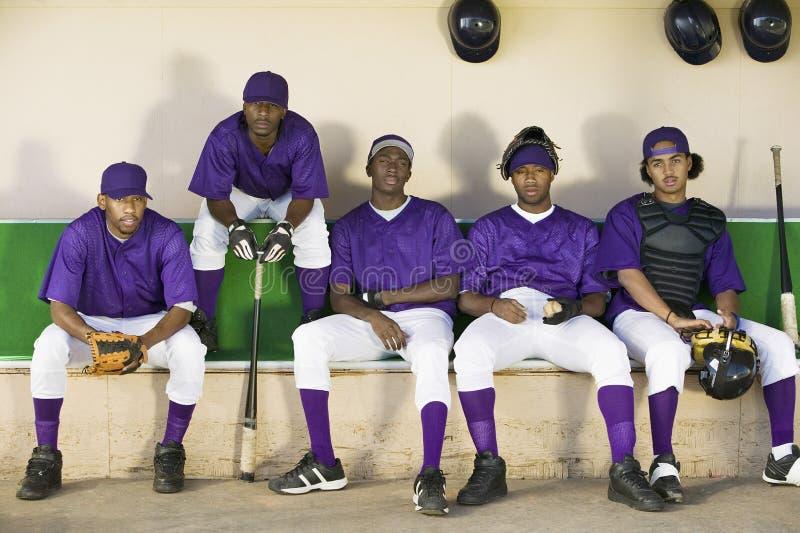 Honkbalspelers die in Dugout zitten stock fotografie