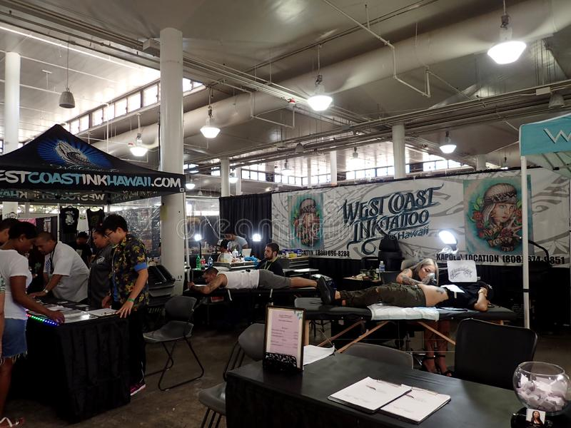 Eople lays on tables as they get tattoo from men. Honolulu - August 6, 2017: People lays on tables as they get tattoo from men at the Hawaii Tattoo Expo royalty free stock photo