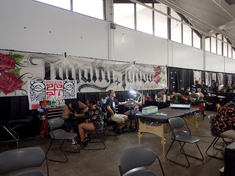 People sit and get arm tattoos at the Hawaii Tattoo Expo. Honolulu - August 6, 2017: People sit and get arm tattoos at the Hawaii Tattoo Expo stock photo