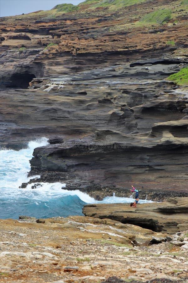 Honolulu, Hava? - 4/27/2018 - jovem mulher que exercita na linha costeira da rocha vulc?nica de Oahu, Hava? fotografia de stock
