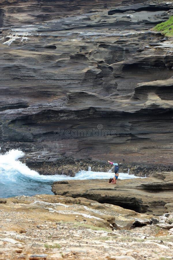 Honolulu, Hawa? - 4/27/2018 - Jonge vrouw die op de vulkanische rotsoever uitoefenen van Oahu, Hawa? stock fotografie