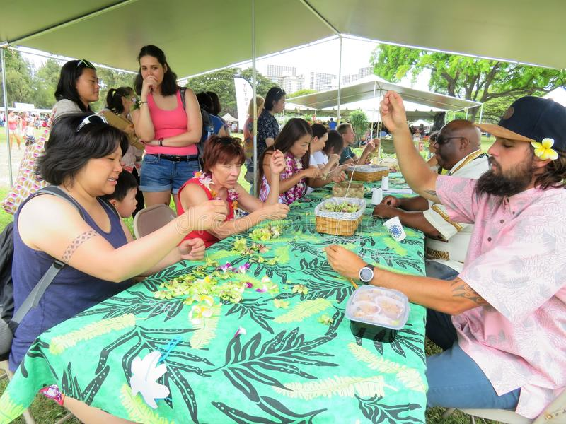 Honolulu, Hawaii - 5/2/2018 - Tourists learning the fine art of lei making in Hawaii royalty free stock photography