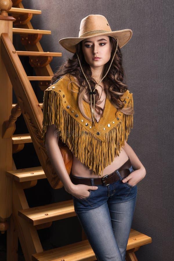Honom flicka i dräkten av en cowboystående arkivfoton