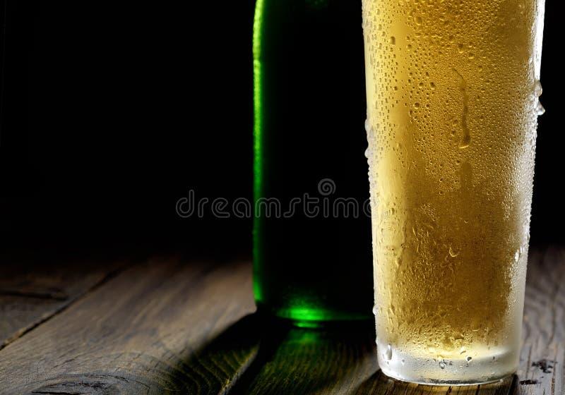 Honom kallt skummigt öl i ett exponeringsglas och en grön flaska på en mörk träbakgrund arkivfoto