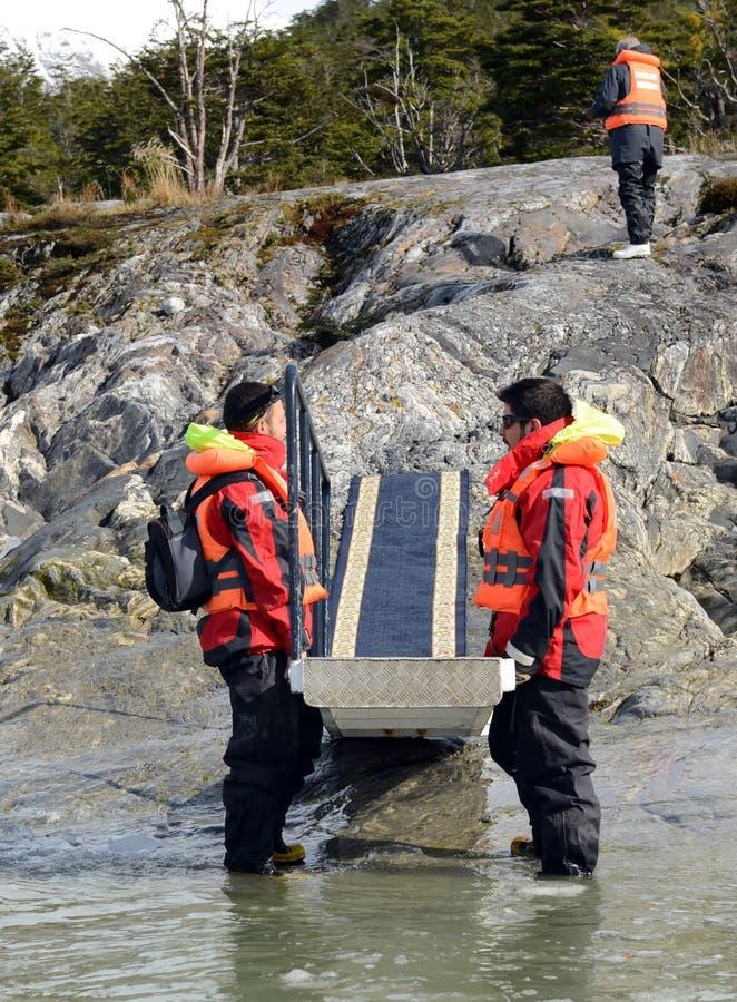 Honom män som rymmer stegen för disembarkationen av turister från kryssningskeppet - till - kust nära Pia-glaciären arkivfoton