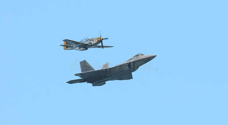 Honor Flight. An honor flight, commemorating the heritage of generations of design and development in US air power, featuring a P-51 Mustang and an F-22 Raptor stock photos