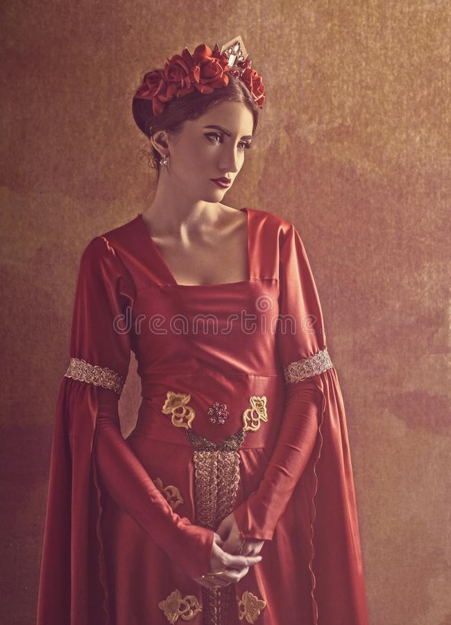 Honor and pride. Female portrait with medieval dress and crown. Grungy background stock photos