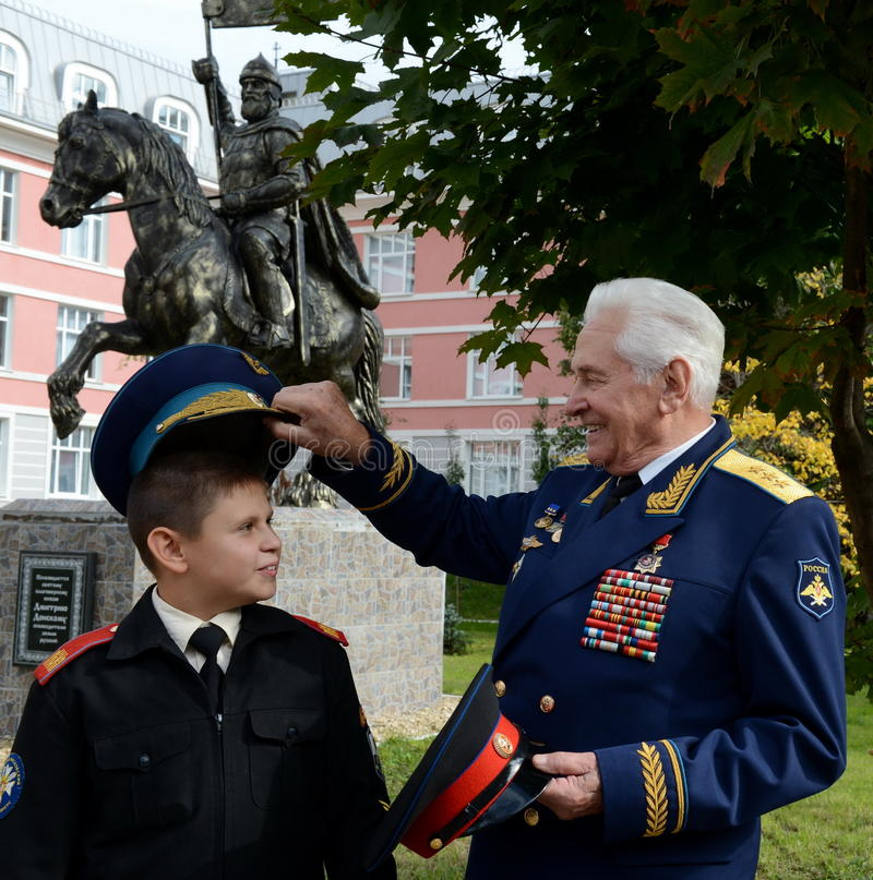Honored military pilot, colonel general of aircraft Nikolay Moskvitelev with the Moscow cadet. MOSCOW, RUSSIA - SEPTEMBER 1, 2014:Honored military pilot stock image