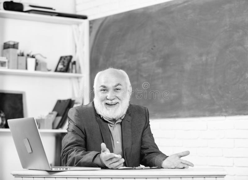Honored professor. Teacher bearded man tell cheerful story. Teacher charismatic grandpa sit at table classroom royalty free stock images