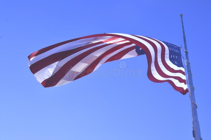 American flag flying at half staff or half mast. Honoring the dead during a national lost or grief of the nation the American flag is lowered to half staff or royalty free stock images