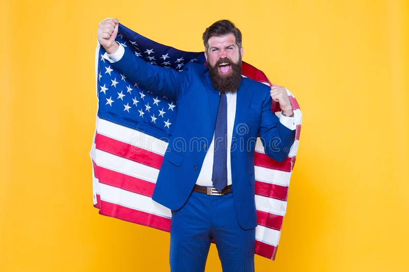 Honour and glory to my country. Happy businessman holding old glory american flag on yellow background. Bearded man in. Formalwear enjoying glory and success royalty free stock photo