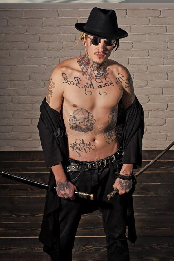 Honra e dignidade Guerreiro no chapéu negro e na roupa aberta que mostram o torso tattooed imagens de stock royalty free