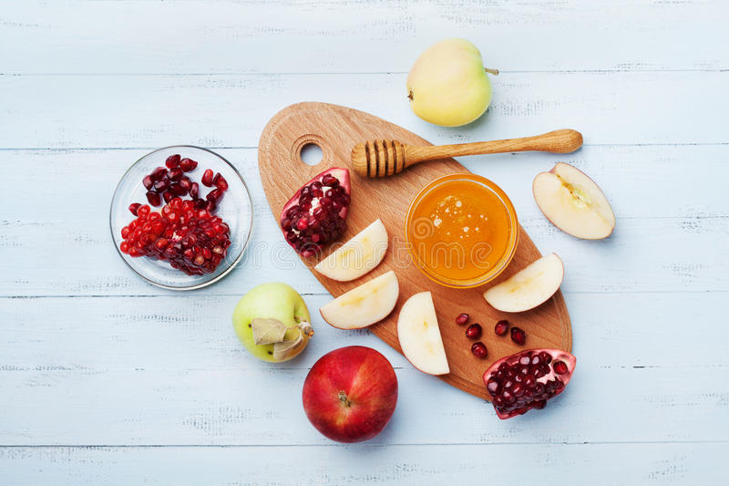Honung, äppleskivor och granatäppleserven på kök stiger ombord bästa sikt Tabelluppsättning med traditionell mat för judisk ferie royaltyfri foto