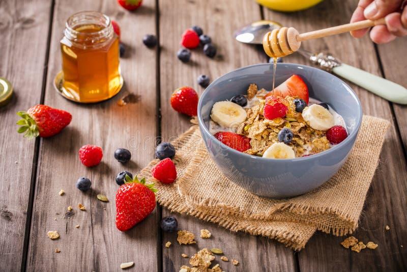 Honung för lantlig hand för frukostsädesslag virvlande runt royaltyfria foton