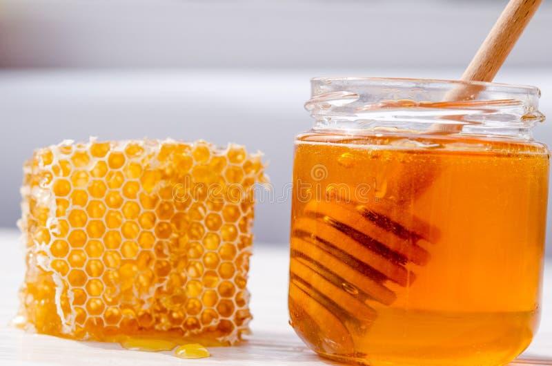Honung i en exponeringsglaskrus, inom en träsked för honung Honungskaka med honungdroppar arkivfoton