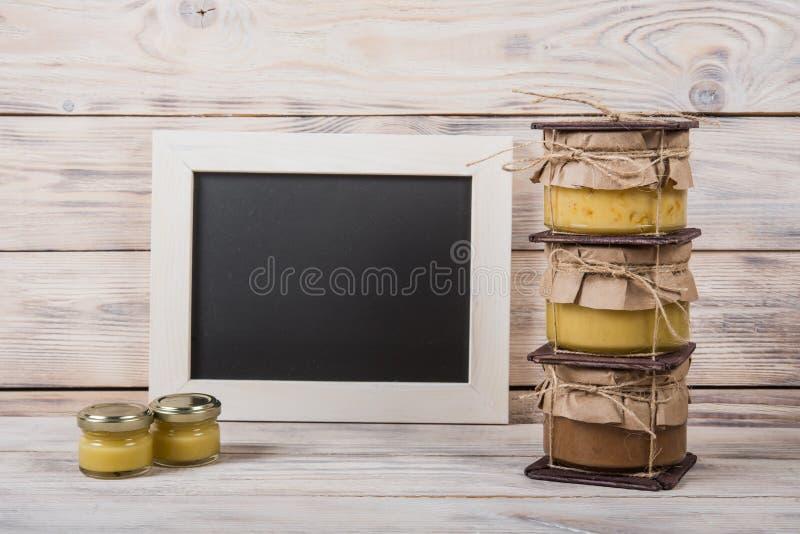 Honung i en glass krus på en ljus träbakgrund med en chalkbo royaltyfri foto