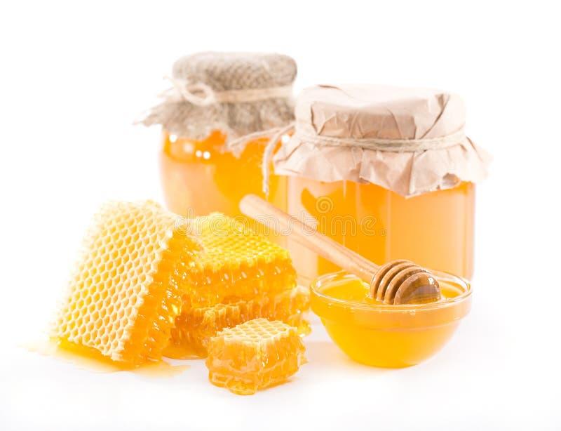 Honung i en krus och en honungskaka royaltyfria foton