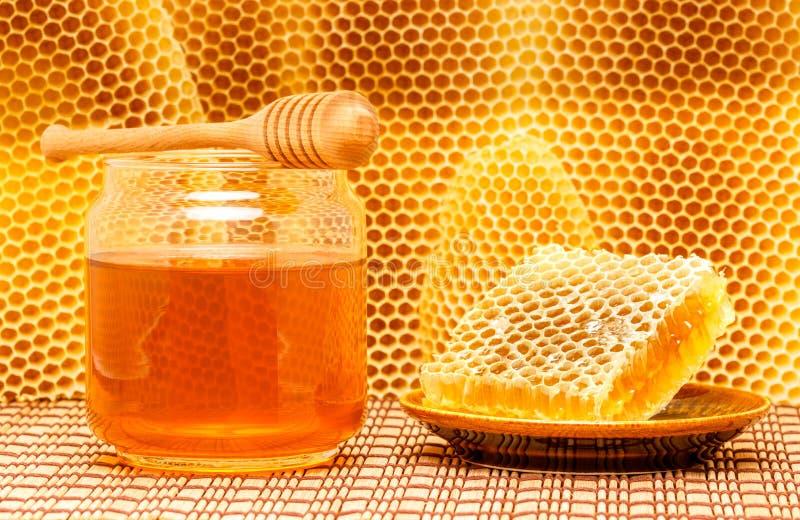 Honung i krus med skopan och honungskakan på mattt arkivfoto