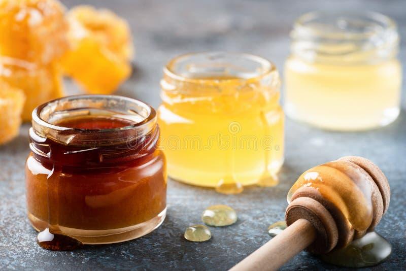 Honung i krus med trähonungskopan, vätskehonung royaltyfria bilder