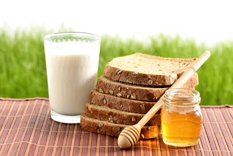 Honung och mjölkar med bröd royaltyfria foton
