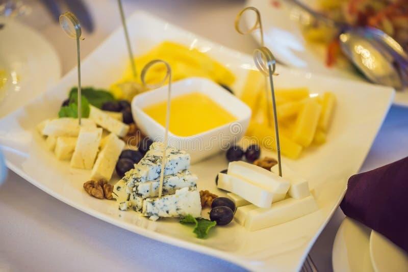 Honung och ostar på en vit platta, mat royaltyfria bilder