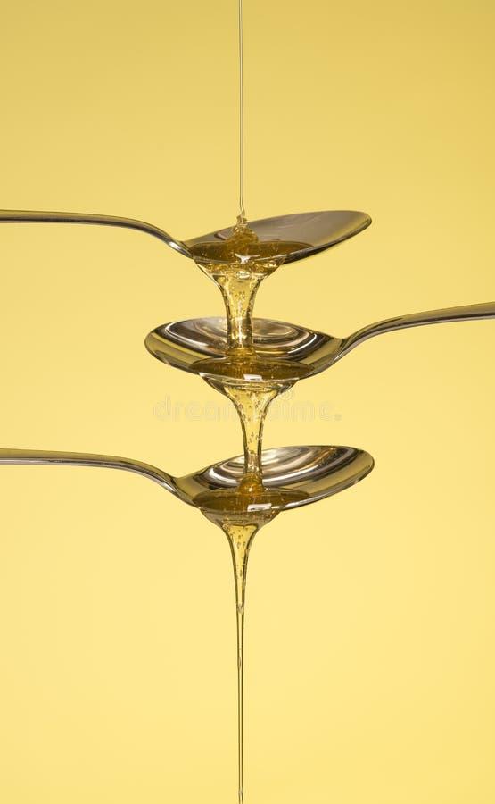 Honung som häller över tre skedar arkivbild