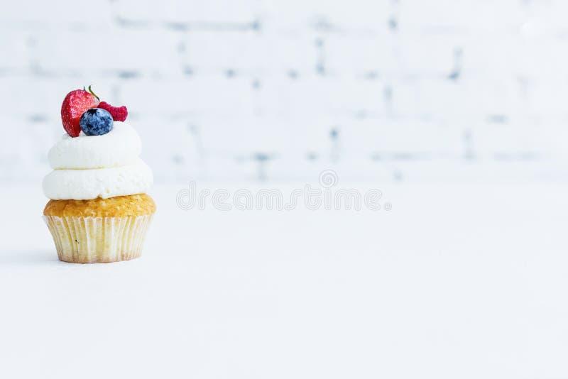 Honungcapcake med mascarponekräm med blåbärjordgubbar och hallon arkivbilder