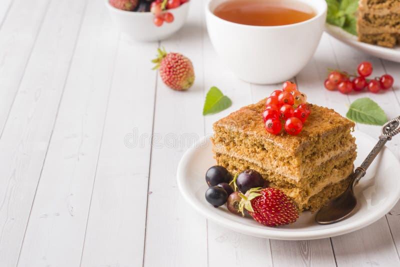 Honungkaka med jordgubbar, mintkaramellen och vinbäret, en kopp te på en ljus bakgrund royaltyfria foton