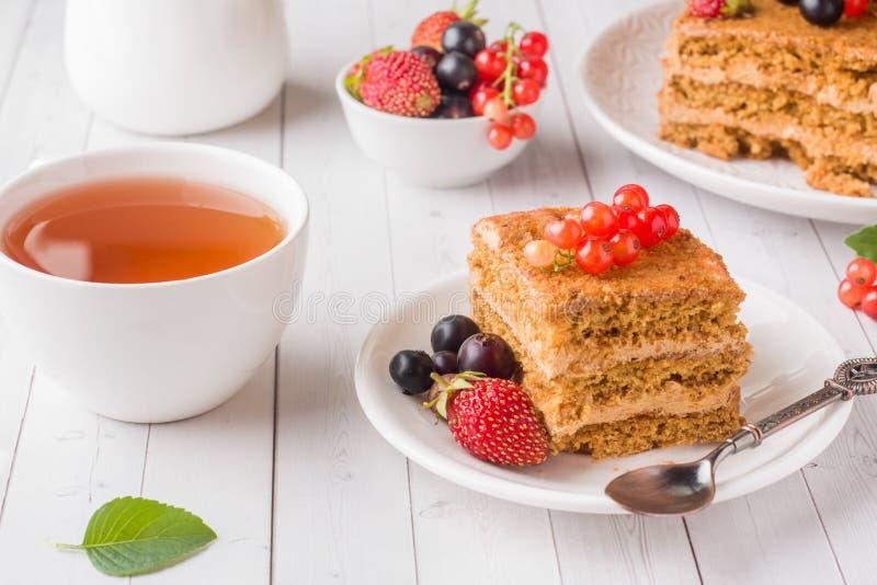 Honungkaka med jordgubbar, mintkaramellen och vinbäret, en kopp te på en ljus bakgrund royaltyfria bilder