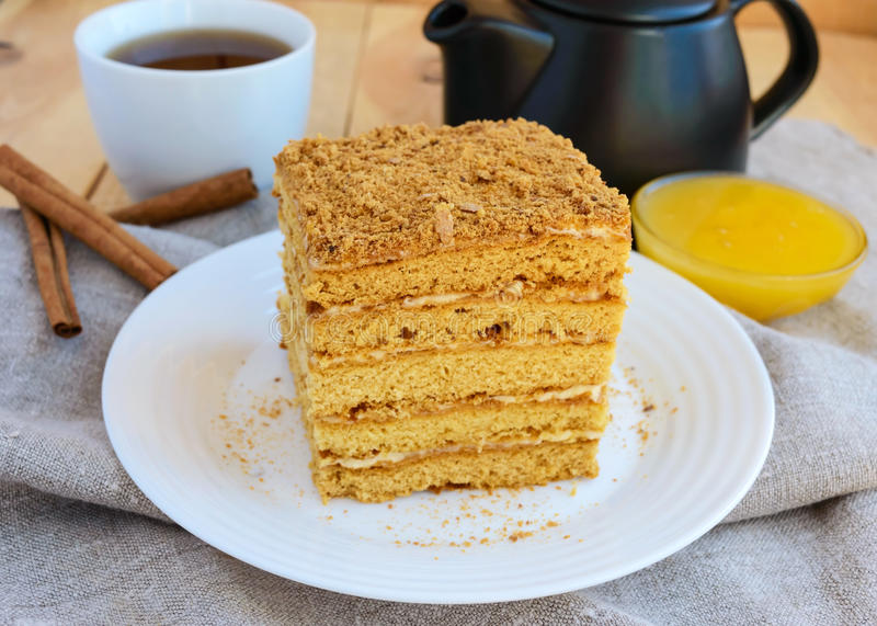 Honungkaka och kopp te på träbakgrund Klippa ett stycke arkivfoto