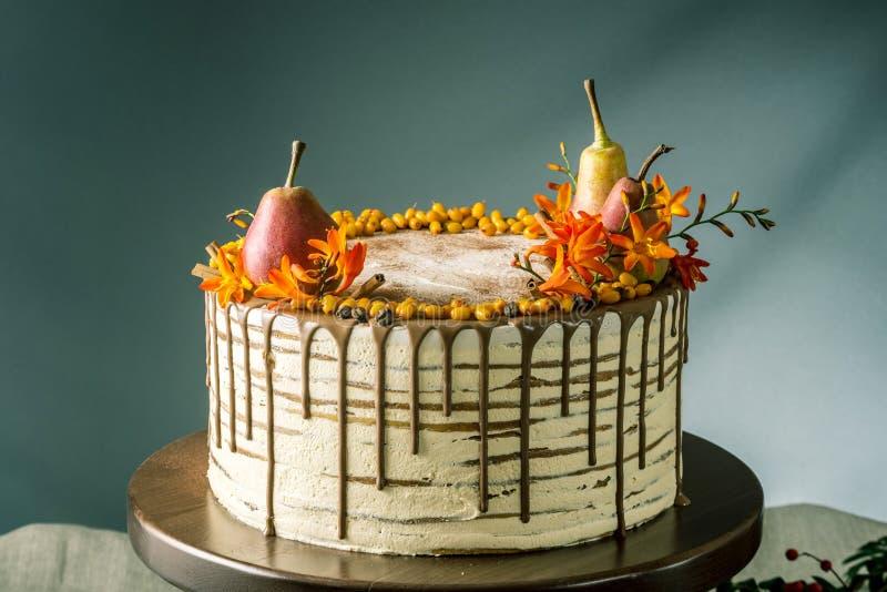 Honungkakan häller över chokladen och dekorerat med päron och havsbuckthornen på en trätabell Söt höststilleben fotografering för bildbyråer