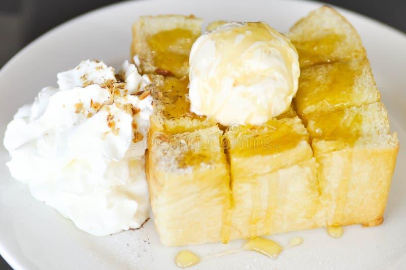Honungrostat bröd med vaniljglass, piskad kräm och sirap royaltyfri bild