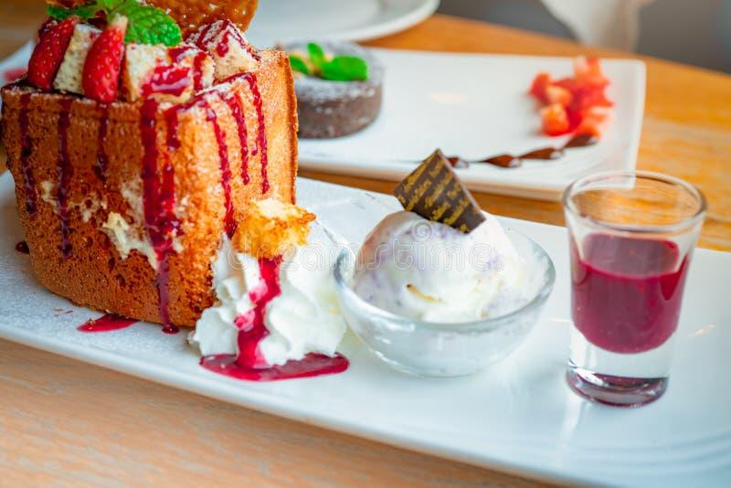Honungrostat bröd som överträffar med jordgubbar, en sida av piskad kräm, vaniljglass Brödrostat bröd på den vita maträtten på su arkivbilder
