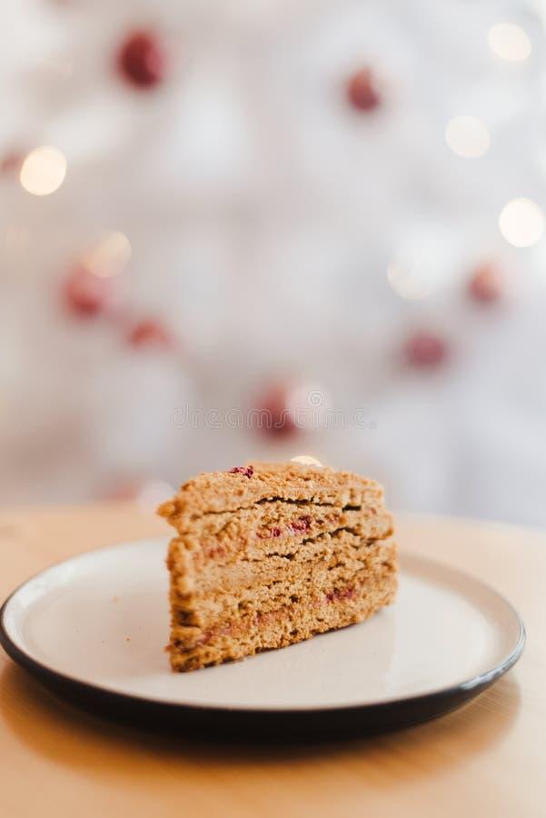 Honungskakan på bordet nära den vita julgranen med gyllene bokeh-ljus arkivbild