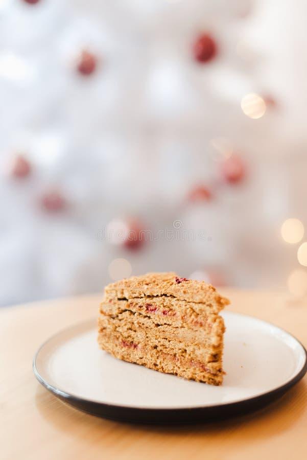 Honungskakan på bordet nära den vita julgranen med gyllene bokeh-ljus royaltyfri bild