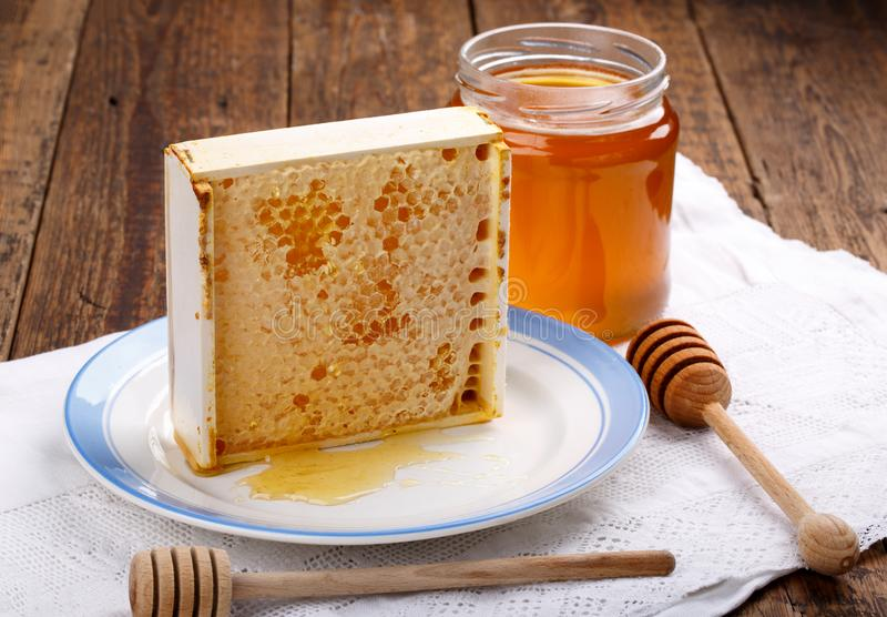 Honungskakor med honung och kruset av honung arkivfoto